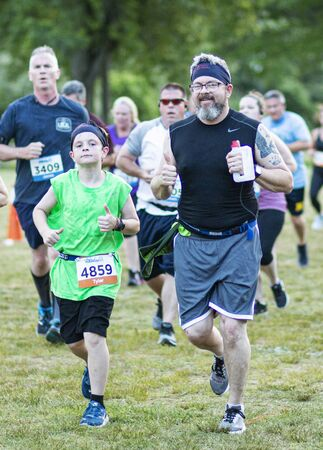 Kings Park, New York, USA - 17 June 2019: A father and son give the thumbs up sign while running a 10K trail race during the NY state parks Sunken Meadow summer series race.