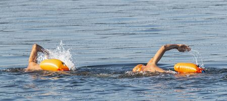 Two male triathlets training partners swimming together in the blue long island sound.