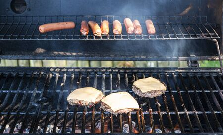 Hot dogs and cheesburgers are cooking on a coal grill during a summer barbeque.