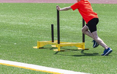 A young male runner is pushing a yellow sled on a green turf field at running camp.
