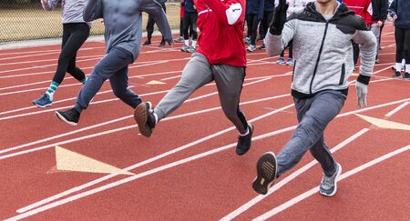 A high school track team is performing straight leg bounding drills on a red track during winter practice.