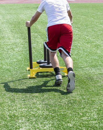 A teenage boy is pushing a yellow sled with weights on it during running camp on a green turf field.