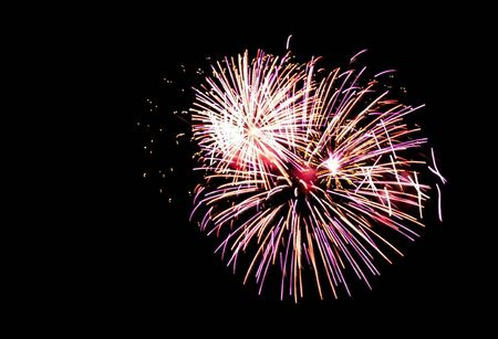 Colorful fireworks light up the night sky during at the end of a concert in park.