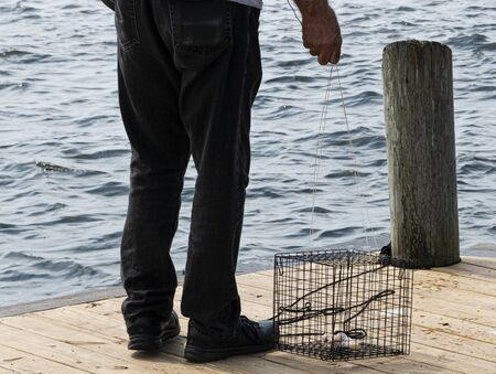 A man getting ready to throw his crab trap into the water off of a wooden pier. Stock fotó