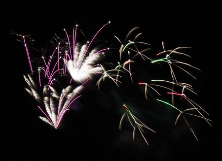 Fireworks display of pink, green and white fireworks fill the sky during a show on a summer night. Imagens