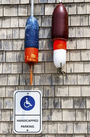Handicapped Parking Only sign on a wall in Maine with lobster buoys  hanging above it. Imagens