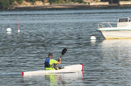 A man is kayaking in a harbor on the north shore of long island paddling around moored boats. Imagens