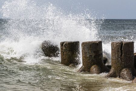 Atlantic Ocean waves croshing on to a jetty sticking out in to the water from the beach on the Fire Island National Sea Shore. Imagens