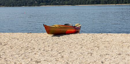 A single orange kayak on the sand of the beach with blue water in the background.