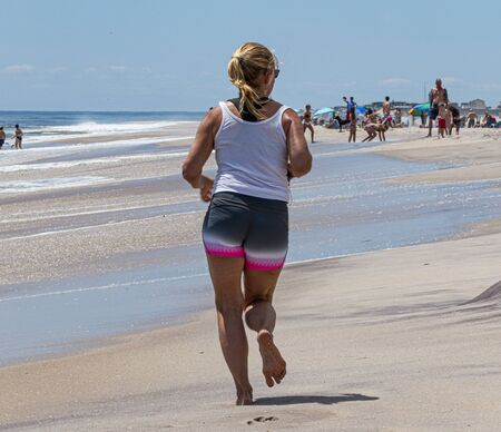 A young women is running barefoot on the sand of a beach  on Fire Island close to the water.
