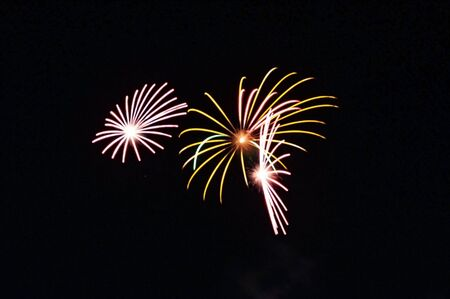 Three colorful bursts of fireworks close together during a fireworks show on a summer night.