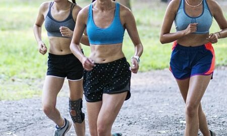Three teenage girls training together running on a gravel path on a hot summer early evening. Stockfoto