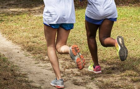 Two runners are training together on a grass and dirt path in a county park from the waist down. Stockfoto