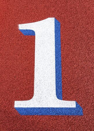 A 3d large block number one is painted on a red track with blue trim.