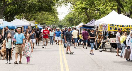 Babylon, New York, USA - 1 June 2019: People walking around and enjoying a street fair with vendors selling artwork and home goods in Babylon New York Long Island.