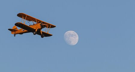 An antique american bi plane foing a fly over at dusk with full moon and a blue sky.
