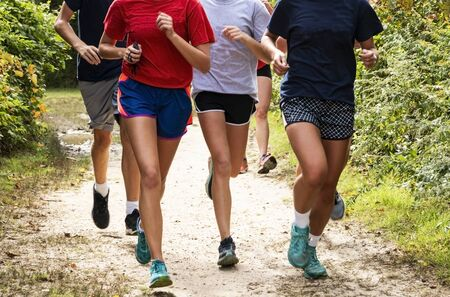 A group of boys and girls cross country runners training together on a dirt path in a local park on a dirt path surrounded by bushes.