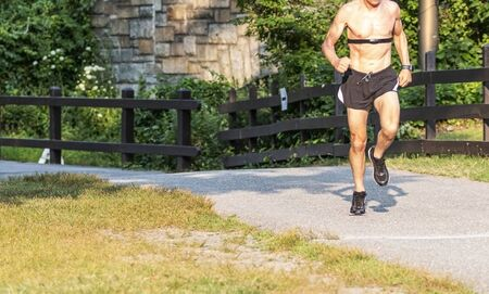 Runner on a path in a park is shirtless and wearing a heart rate monitor on his chest on a sunny day.