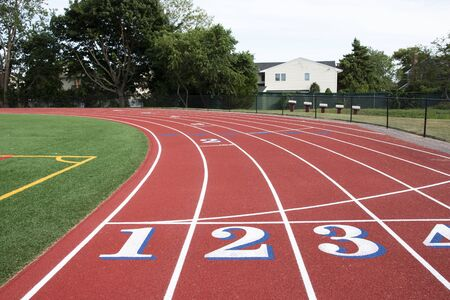 A high school tracks common start finish line with white numbers that have blue trim looking into the first turn.