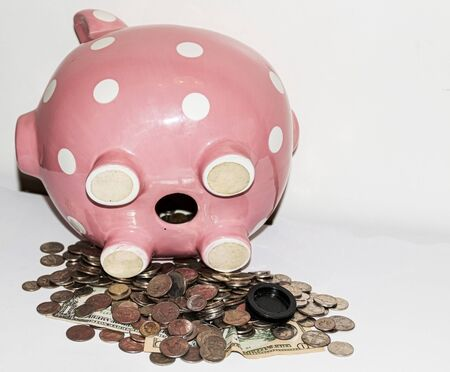 Money falling out of a pink piggy bank with white polka dots which is laying on its side with a white background.