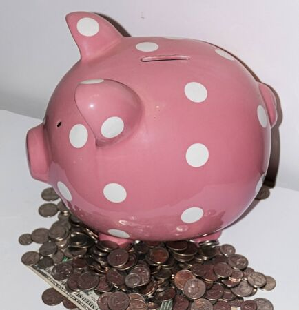 A ping piggy bank with white polka dots standing on top of many coins and dollar bills in front of a white background.