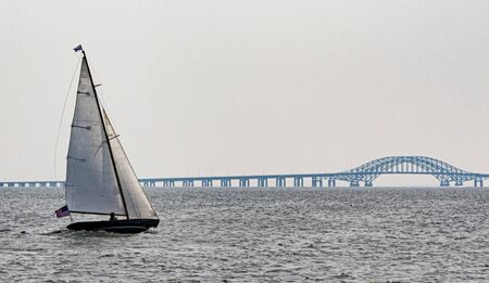 An individual is sailing in his sailboat moving toward the Robert Mosses Bridge in the Great South Bay Babylon New York off of Long Island. Imagens