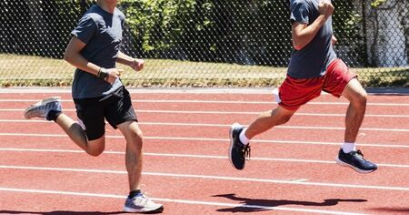 Two boys racing each other running clockwise on a red track on s sunny summer day.