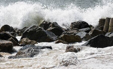Stones on the shore next to a jetty of rocks have waves crashing on them and water flowing over them. Imagens