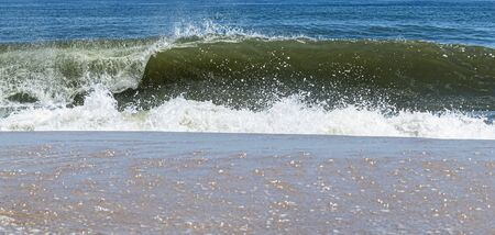 An Atlantic Ocean wave curling to the right is crashing on to the shore of Fire Island New York.