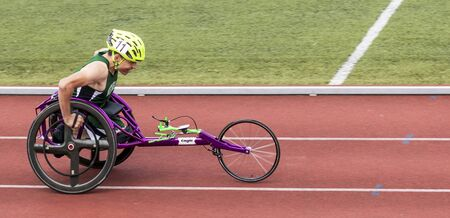 Middletown, New York, USA - 7 June 2019: A High school track and field wheelchair athlete competing in a track and field meet with his purple wheelchair.