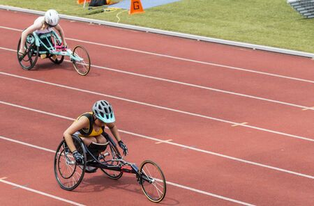Middletown, New York, USA - 7 June 2019: Two high school wheelchair athletes racing each other in lanes on an outdoor track. Redactioneel