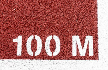 100 M is painted at the start line of the dash on a red track. Imagens