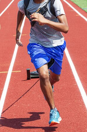 Close up of a teenage boy is running on a red track while pulling a wieghted sled during track and field practice.
