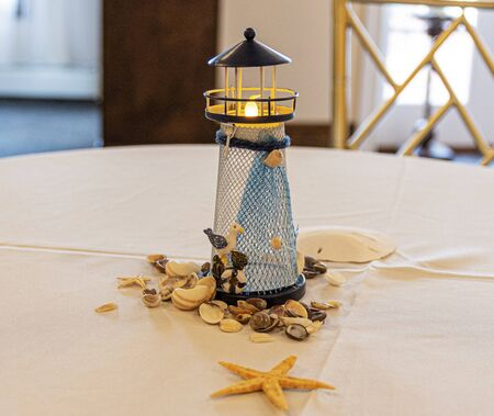 A small lighthouse with shells used as table decortaion at a party.