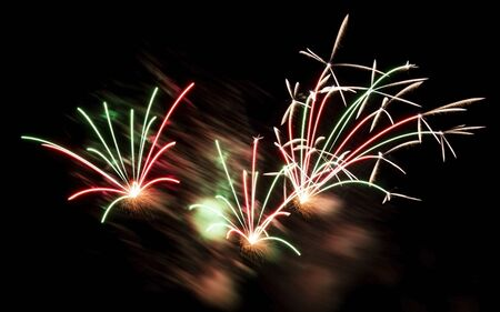 Fireworks become blurred by the wind during a fireworks show at night.