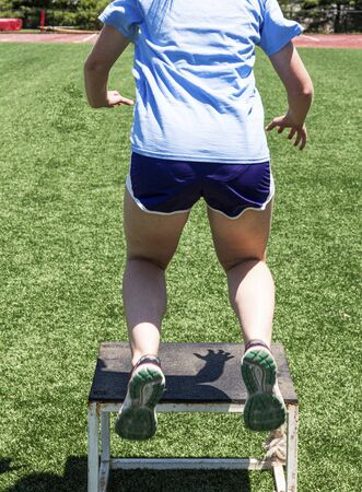 A high school female athlete jumping onto a plyo box during strength and agility practice.