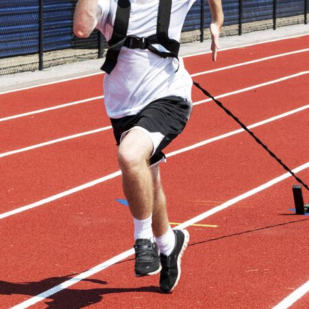 A high school male track and field athlete is pulling a sled with weights on a red track during strength and agility practice. Imagens
