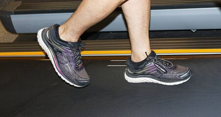 Runners lower legs and feet running on a treadmill indoors.