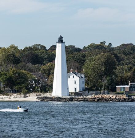 A small motor boat is heading into harbor passing the New London Lighthouse in the Long Island Sound. Imagens