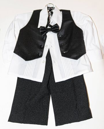 Toddlers tuxedo with a black vest over a white shirt with a white backgound hanging on a hanger with no jacket.
