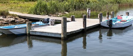 Two motor boats tied to a dock on the shore of the Great South Bay on Long ISland.
