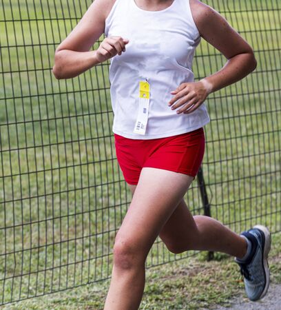 A high school female cross country runner in a white and red uniform running next to a wire fence during a 5K race.