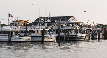 Bay Shore, New York, USA - 1 June 2019: Fishing charter boats with seagulls flying over are docked and filling with people ready to go fishing at Captree Boat Basin, New York.