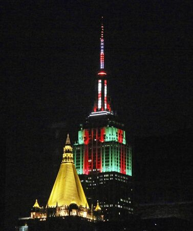 New york, New York, USA - 1 January 2016: The top of the Empire State building is light up in green and red for Christmas behind the Gold top of the Chrysler building on January first 2016..