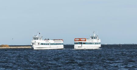 Bay Shore, New York, USA - 8 June 2019: Two passenger ferries pass each other as one heads to Fire Island and the other heads back to Bay Shore.
