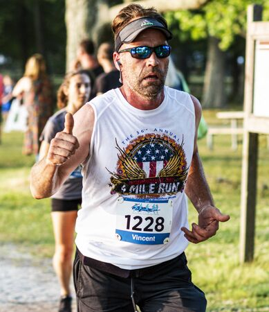 North Babylon, New York, USA - 8 July 2019: A man running a 5K race around Belmont Lake State Park gives the photographer a thumbs up.