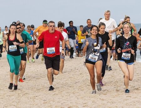 Babylon, New York, USA – 24 June 2019: Many people running a one mile race on the beach by the water at the Robert Mosses State Parks summer series. Editöryel