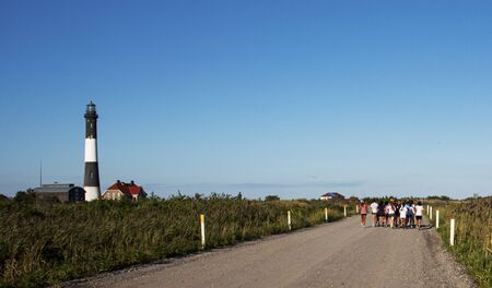 A group of girls are running on the dirt road with the Fire Island Lighthouse and blue sky in front.