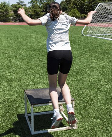 A teenage girl is perfomiing a box jump on a turf field during track and field summer camp practice.  Imagens