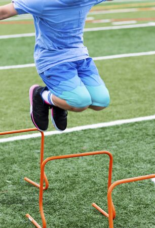 A young boy is jumping over an orange plastic mini hurdle on a green turf field at Track and Field summer camp.